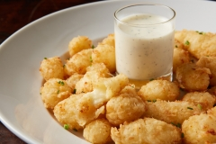 Fried cheese curds served in a white bowl with ranch dipping sauce on a dark wood table.