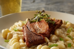 Roasted pork belly served on top of creamy macaroni and cheese with a pilsner beer in the background on a grey metal table.
