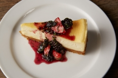 Slice of cheesecake with fresh berry sauce of strawberries, raspberries and blackberries dripping over the top sitting on a white plate on a rustic wood table.