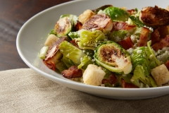 Salad of grilled brussel sprouts tossed with bacon, croutons and cheese.